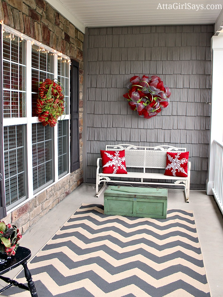 side porch decorated for Christmas with snowflake pillows and gray chevron rug and antique toolbox