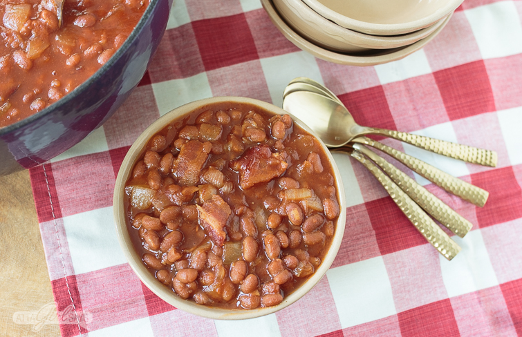 This southern baked beans recipe is a family favorite, perfect for cookouts, potlucks and other gatherings where you need to feed a crowd. The combination of bacon, sauteed onions, brown sugar, condiments and beans results in a sweet and tangy side dish that everybody loves. #bakedbeans #cookout #potluck #easyrecipes #familyrecipes #southernrecipes