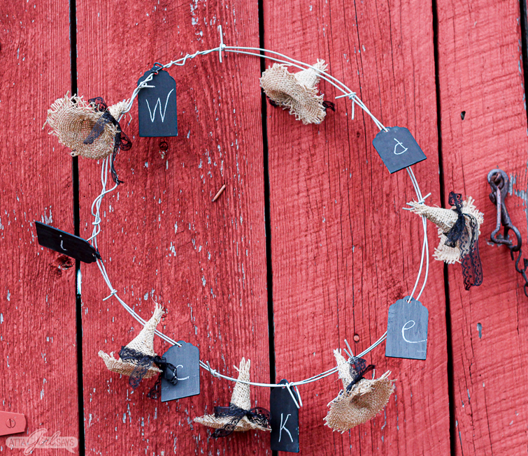 barbed wire wreath spelling out the word Wicked on a red barn door
