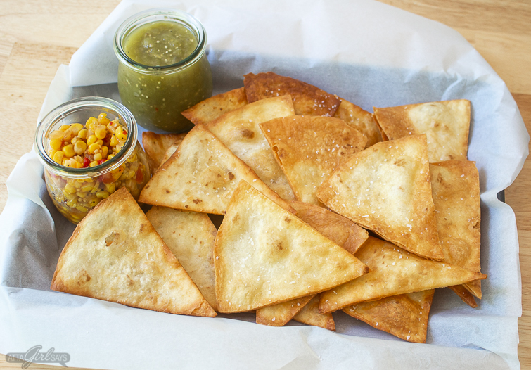 tray of homemade tortilla chips with corn salsa and salsa verde