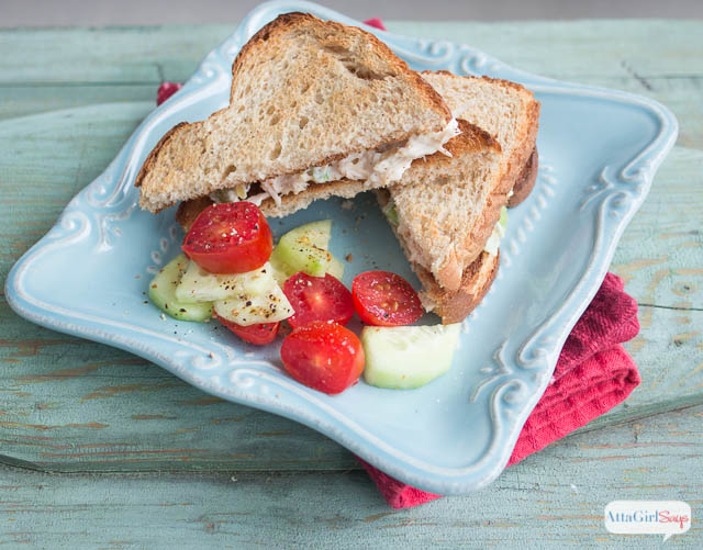 toasted chicken salad sandwich with tomatoes and cucumbers on a plate