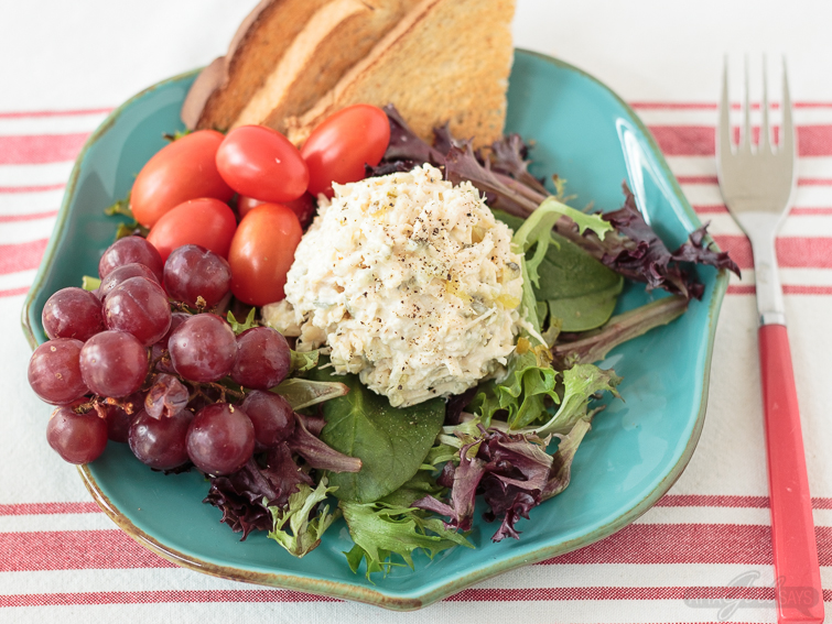grapes, tomatoes and a scoop of traditional chicken salad on a bed of lettuce