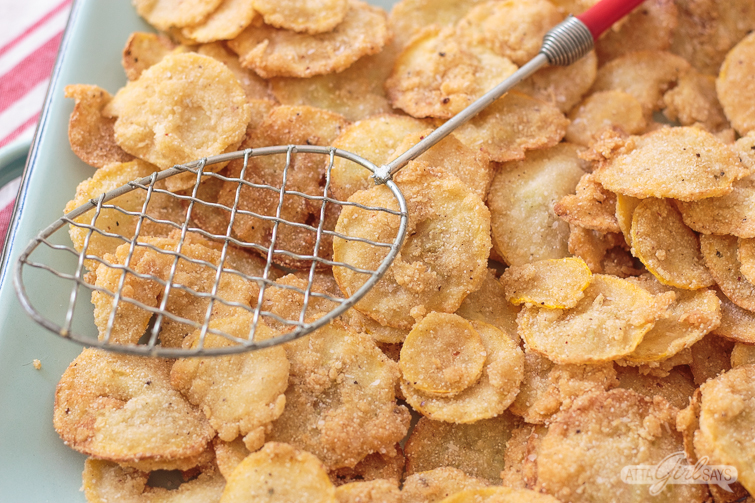 metal spider strainer and fried squash chips on a blue enamel platter