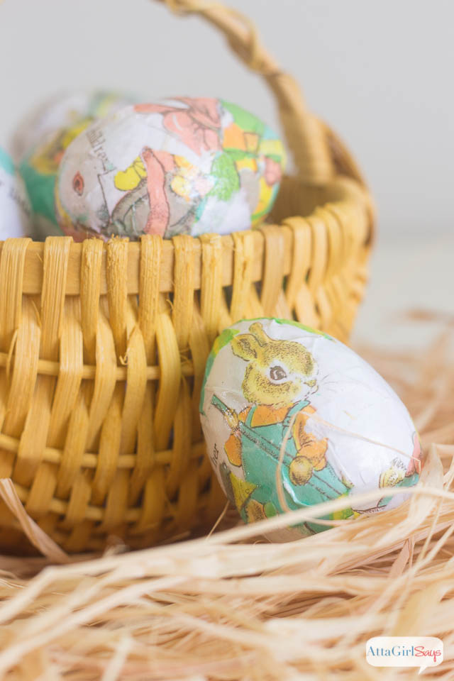 decoupaged Easter egg beside a yellow basket