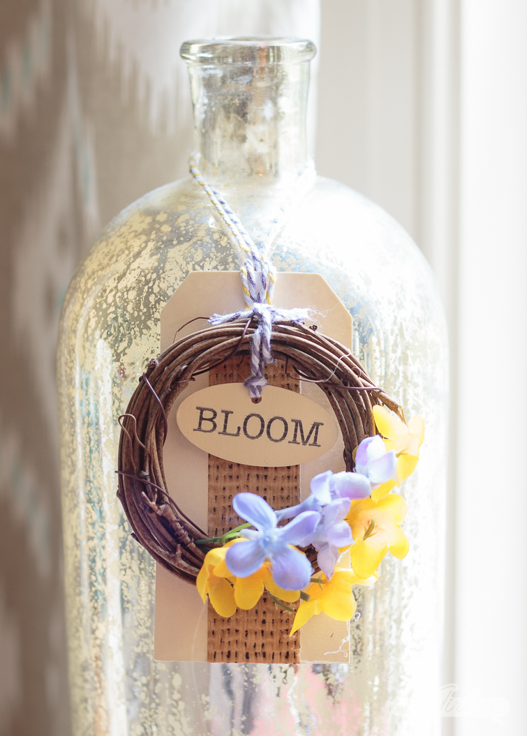 mini grapevine wreath on a tag on a mercury glass bottle
