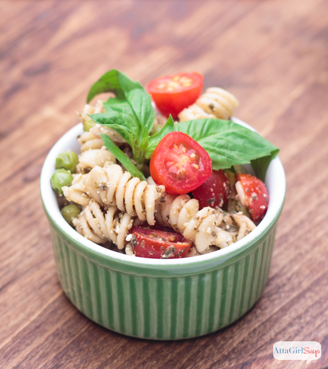 pesto pasta salad with tomatoes and peas in a green ramekin