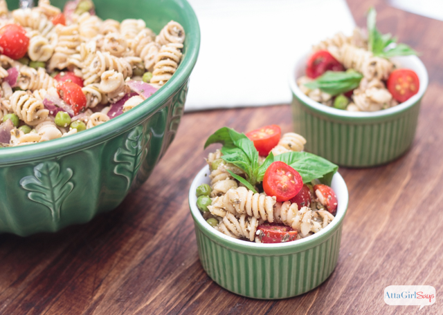 pesto pasta salad with tomatoes and peas in green bowls