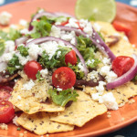 vegetarian nachos with tomatoes, kale, onion, black beans and queso fresco cheese