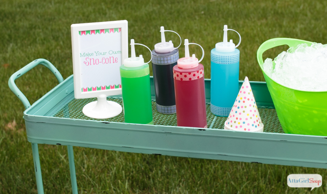 snow cone syrup bottles beside sno-cone cups on a rolling cart