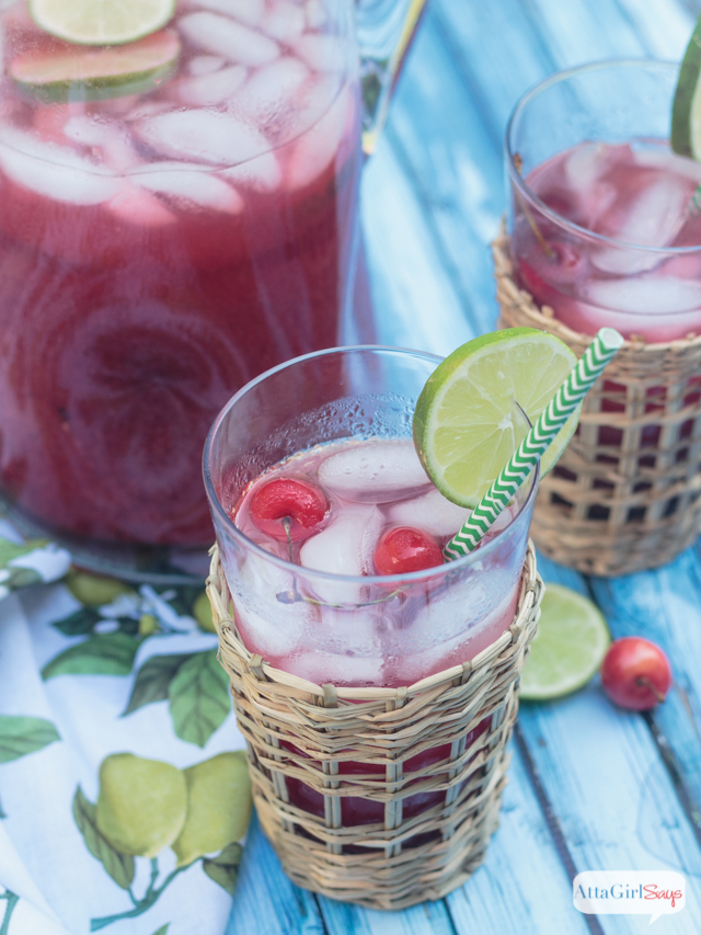 glasses and pitcher of homemade cherry limeade on a blue wooden table