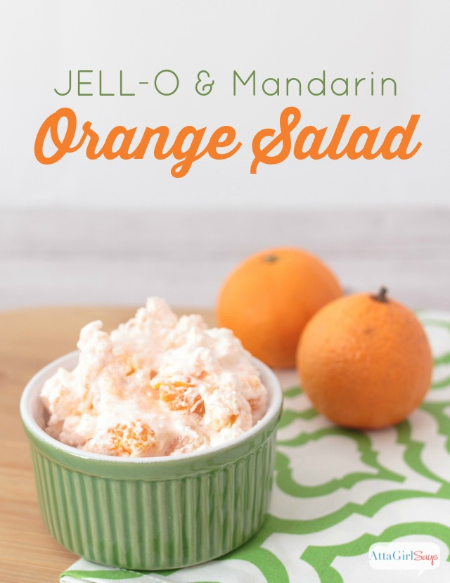 bowl of JELL-O Mandarin Orange salad on a green and white napkin with oranges in the background