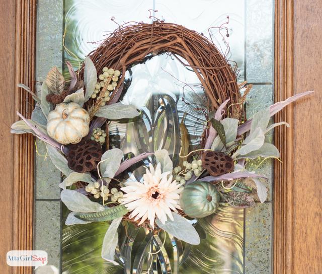 grapevine wreath with pumpkins handing on a glass door