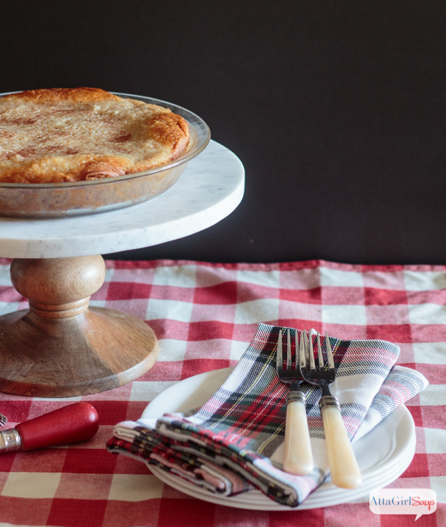 baked homemade applesauce pie on a marble and wood cakestand