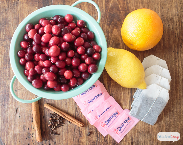fresh cranberries in a colander with cinnamon sticks, lemons, tea bags and sweetener