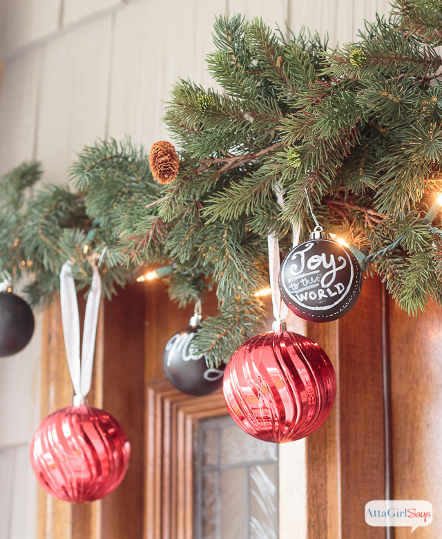 It all started with some gorgeous, wide chalkboard ribbon. Throw in a some vintage Christmas decorations, greenery and ample pops of red, and the result is a gorgeous front porch decorated for Christmas. Who wouldn't want to spend time relaxing in this beautiful space? It's so welcoming and festive!