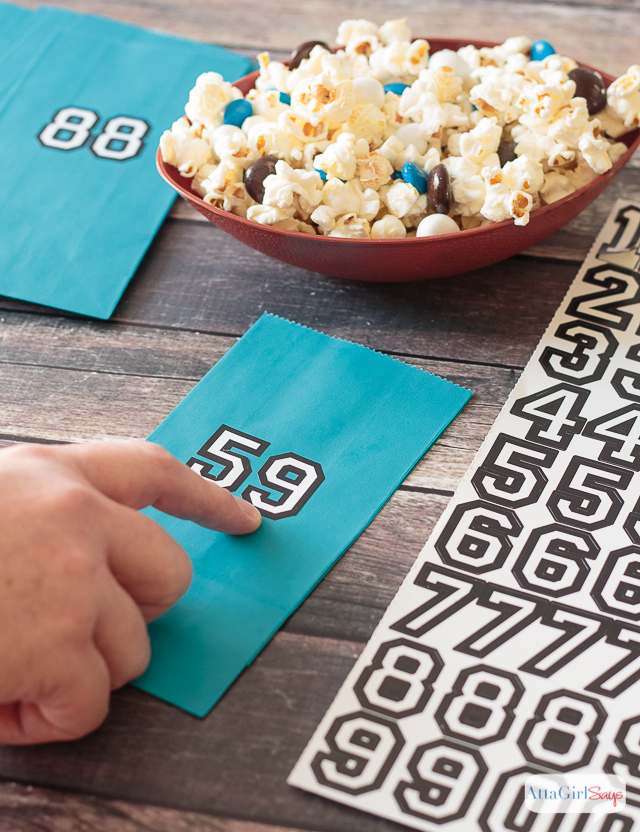 Add this easy-to-make popcorn snack mix to your football party food lineup. Don't forget to serve it in color coordinated bags featuring your favorite players' jersey numbers. #BringtheBOOM #ad