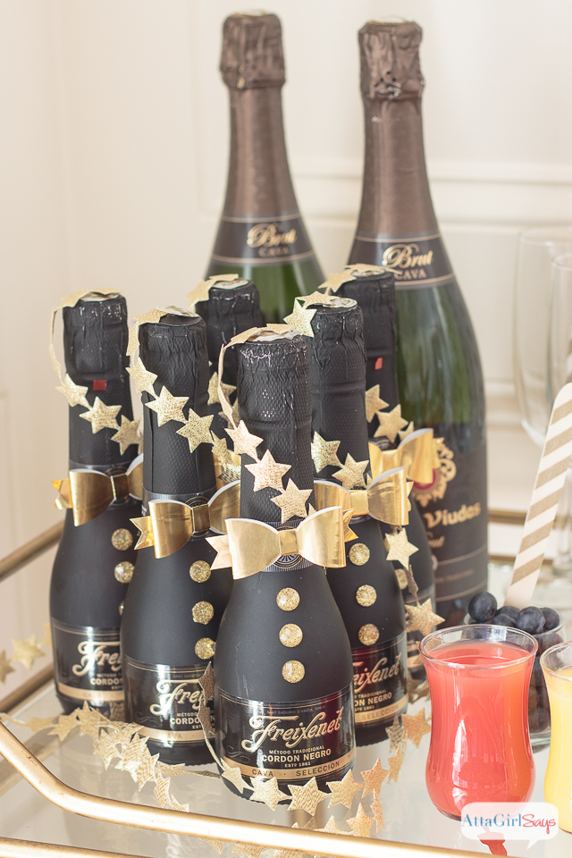 champagne bottles on a gold bamboo bar cart