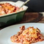 plate of cheesy homemade lasagna beside a casserole dish