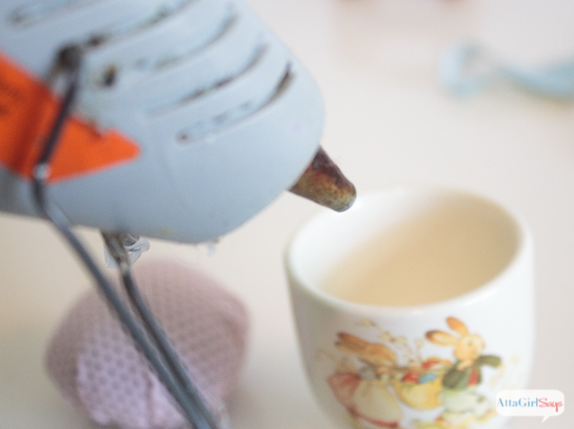 Use a hot glue gun to secure the pin cushion in the egg cup.