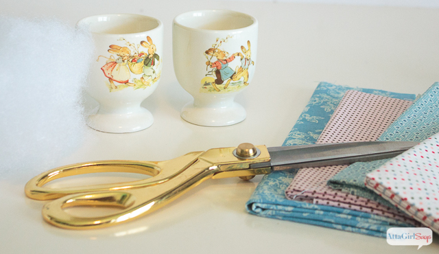 scissors, fabric, egg cups and fiberfill - supplies to make Easter egg cup pin cushions