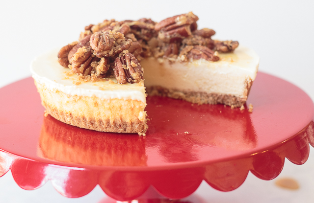 pecan pie cheesecake with a slice taken out on a red cake stand pedestal