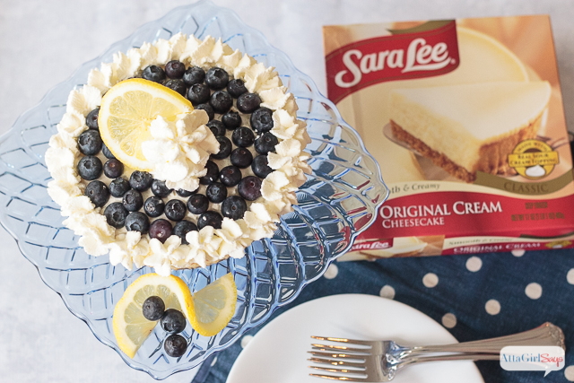 What is it about blueberry and lemon? Those flavors taste so good together, especially on top of a cheesecake! This semi-homemade dessert features a layer of lemon curd, fresh blueberries and homemade lemony whipped cream. #ad #saraleedesserts #pmedia