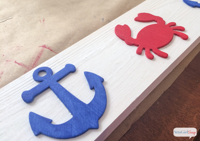 Use scrap wood, paint and inexpensive wooden cutouts from the craft store to create a DIY picture rail to display your favorite vacation pictures and family memories. #decoartprojects #sponsored