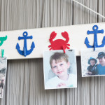 Showcase your favorite vacation memories on an inexpensive DIY photo rail made from a 1X4, wooden cutouts and mini clothespins. #decoartprojects #sponsored