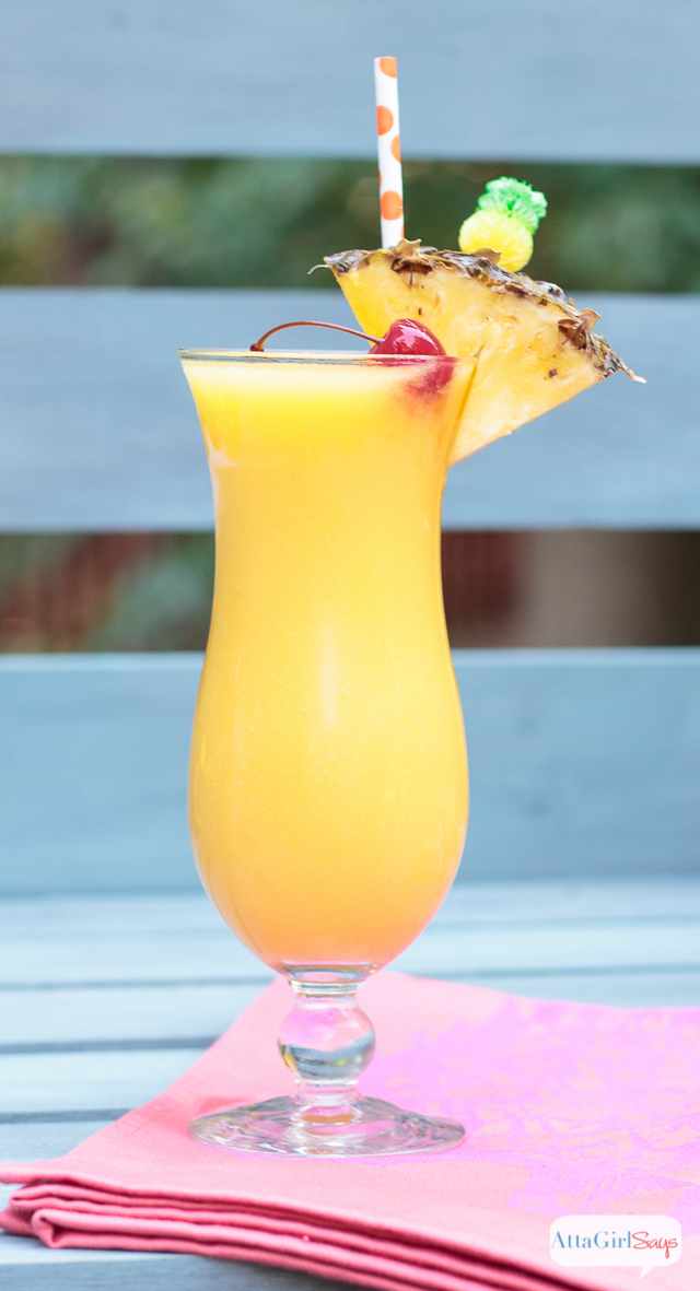 frozen pineapple mango lemonade in a hurricane glass garnished with pineapple and a cherry