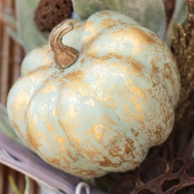 dusty green pumpkin streaked with gold highlights in a grapevine wreath