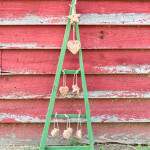 Keep the birds happy and well fed all winter long by making a Tobacco Stick Christmas Tree that doubles as a feeder. Construct a simple frame out of tobacco sticks, paint it and then hang homemade birdseed ornaments from hooks. #sponsored #decoartprojects