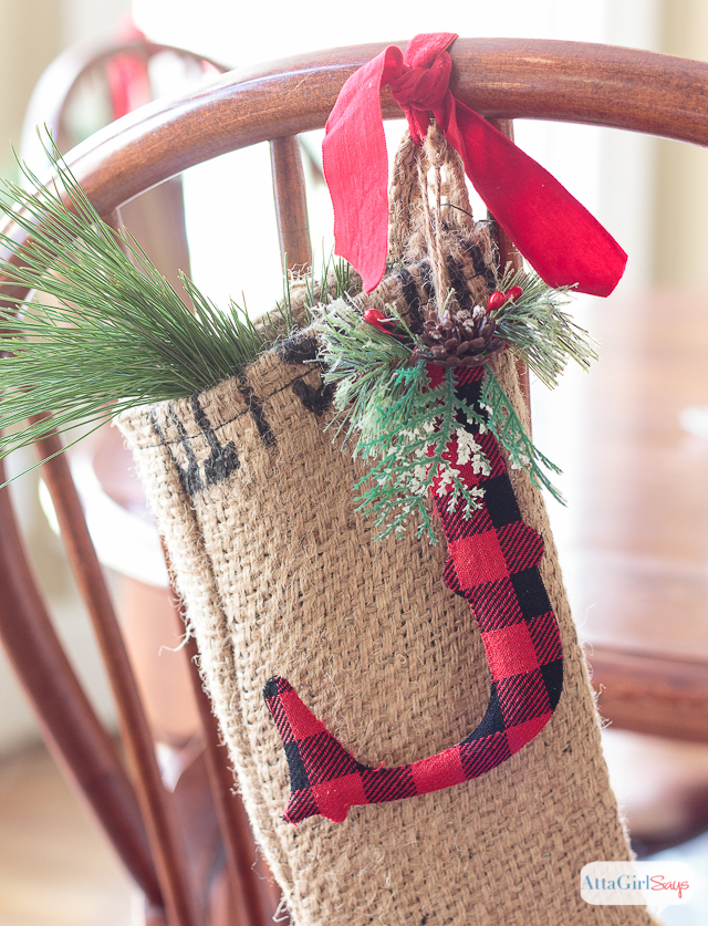 burlap stocking hanging from the back of windsor chair with a buffalo check ornament