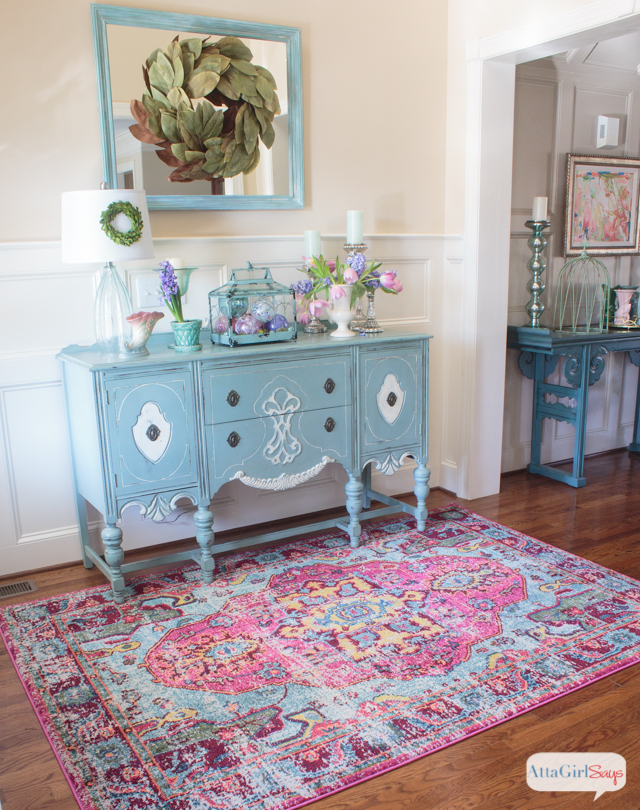 foyer with an aqua blue vintage buffet, oak hardwood floors and a pink and aqua rug