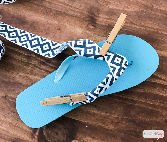 Step 2 for making DIY bow flip flops: Continue wrapping grosgrain ribbon tightly around the strap, over the toe piece and continuing down the other strap. Use clothespins to hold ribbon securely as you work. #sponsored