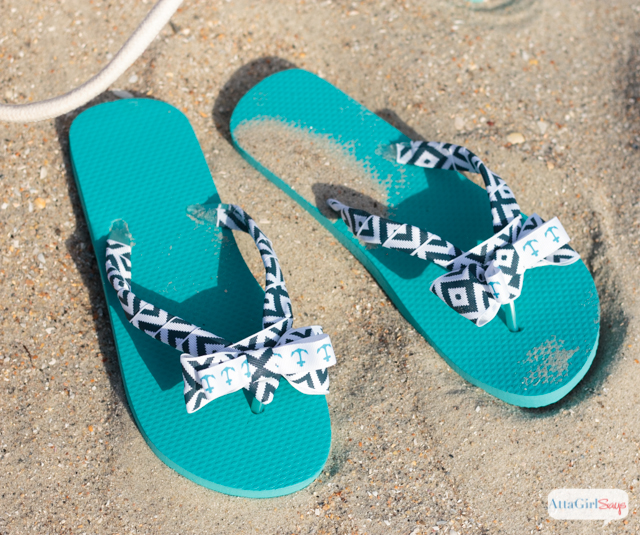 A pair of aqua and navy blue bow flip flops resting in the sand on the beach. #sponsored