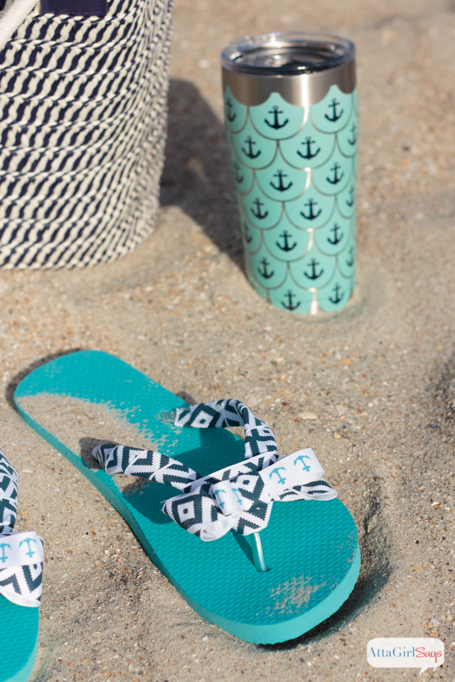 A pair of aqua and navy bow flip flops sits on a sandy beach, alongside a straw beach back and a stainless steel Tervis tumbler decorated with an anchor design. #sponsored