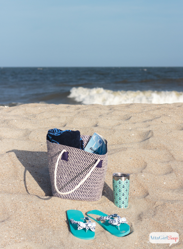 Ocean waves crest on a sandy beach. A straw beach bag packed with a magazine and a beach towel sits on the sand. A pair of sand-covered bow flip flops and a Tervis stainless steel tumbler sits alongside the beach bag with the surf in the background. #sponsored