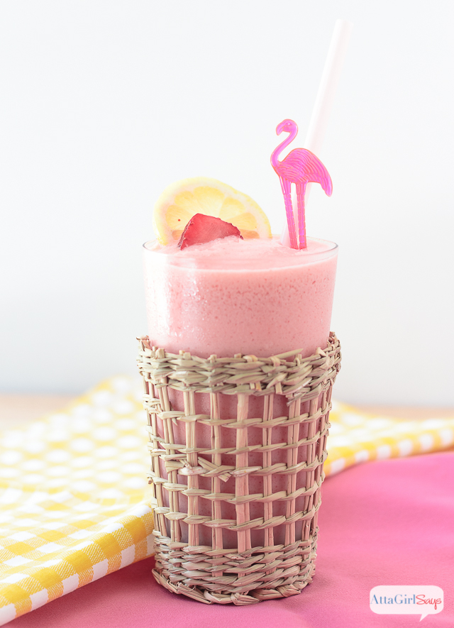 A tall glass of frozen strawberry lemonade garnished with lemon and strawberry slices. Served in a beachy style glass with a pink straw and a flamingo cocktail pick.