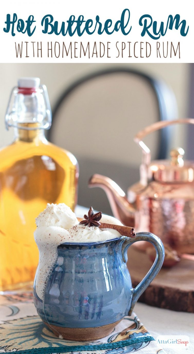 mug of hot buttered rum with rum bottle and copper teakettle in the background