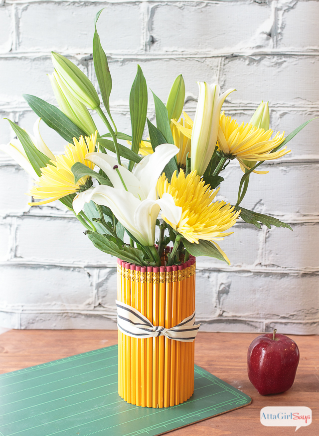 Welcome your favorite teacher back to school with a thoughtful, homemade teacher appreciation gift. This vase is made from dozens of No. 2 pencils affixed to a glass vase. Add a bouquet of gorgeous white lilies and yellow mums. And don't forget an apple!