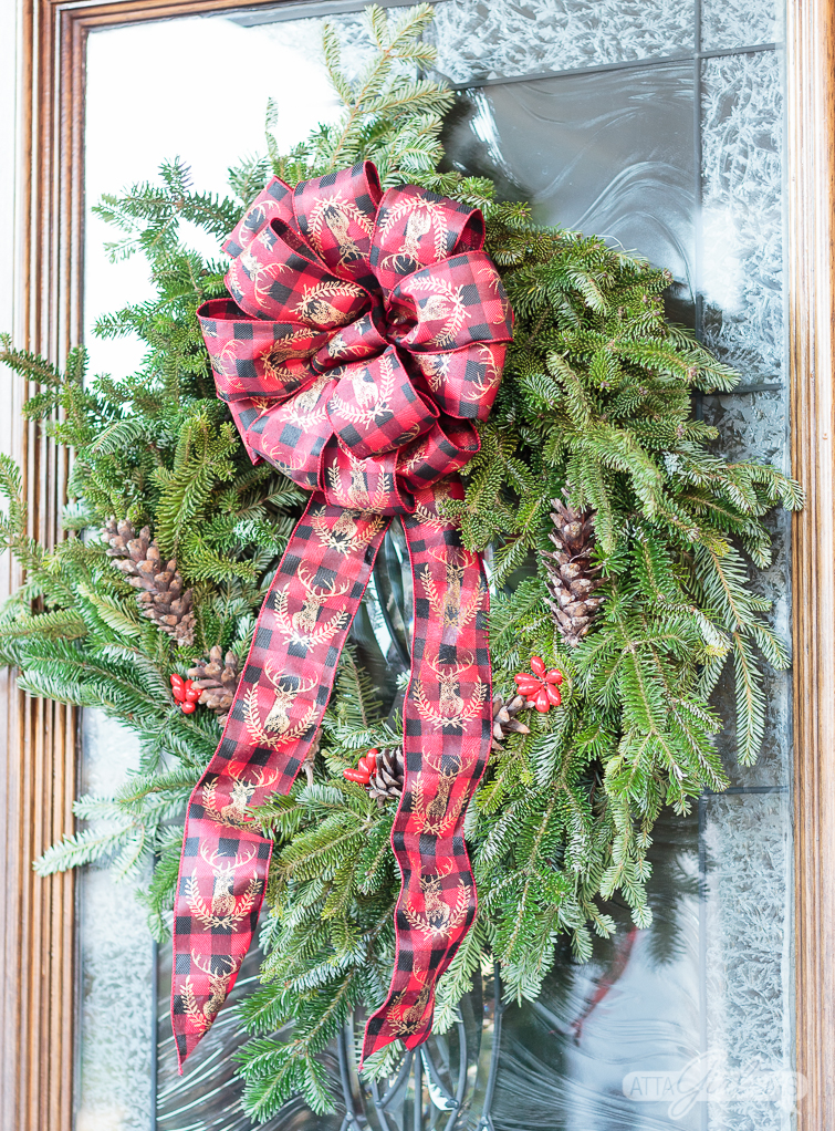 Christmas wreath with a bed and black plaid ribbon