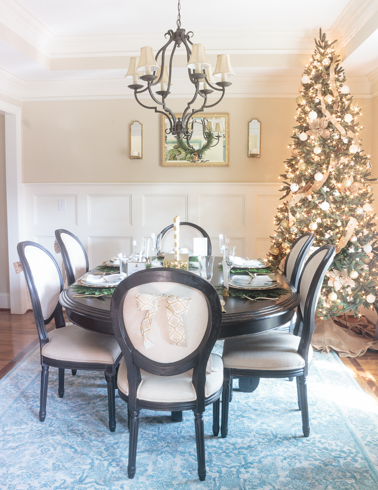 Formal dining room decorated in golden tones for Christmas, with some rustic elements, like pinecones, cotton and burlap mixed in. If you love rustic luxe decor, you have to check out this Christmas home tour.