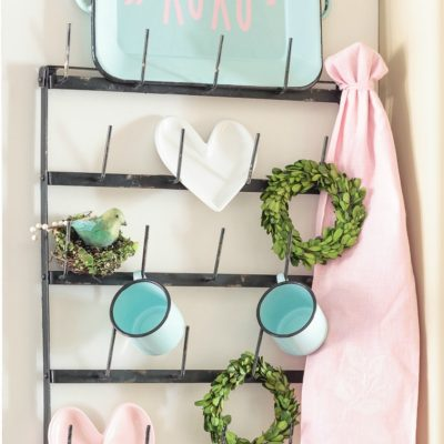 """Dress up your coffee mug wall rack with simple Valentine's Day decor, including a """"Gossip Girl"""" inspired quote you can make with your Cricut. Enamel coffee mugs, miniature boxwood wreaths and heart-shaped plates! Swoon. Click for sources to recreate this look! #mugrack #valentinesday #gossipgirl #xoxo #farmhouse #aquaandpink #mugrackmonday #valentinesdecor #cricutmade #cricutmaker #cricutexploreair #quotes"""