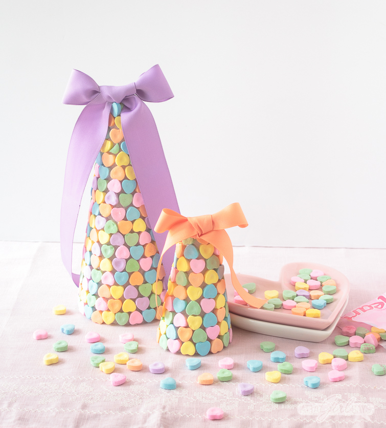 Add a sweet touch to your holiday table with these cute and easy-to-make Valentine candy heart centerpieces made with conversation hearts. #valentinesday #candyhearts #conversationhearts #valentinescrafts #centerpiece
