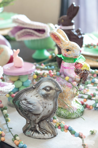 Let this pretty holiday tablescape, featuring pops of pastel and candy, inspire your own Easter table decor. I used chocolate molds, pastel candies, vintage Easter eggs, chocolate bunny figurines to create this sweet seasonal scene. #eastercandy #tablescape #eastertable #springtablescape #tabledecor