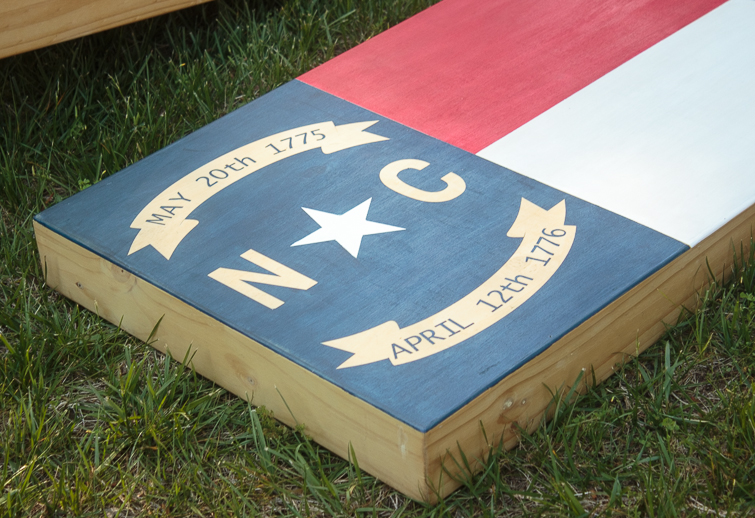 Create your own custom cornhole boards using colored stain and FrogTape. Click for the step-by-step directions on how to make this North Carolina state flag cornhole board design. #ad #cornhole #NCflag #yardgames #summerfun