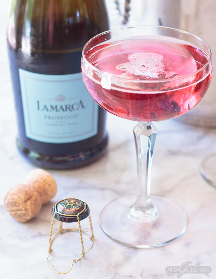 Pink La Marca Prosecco Hibiscus Flower Cocktail in a coupe glass. No special occasion necessary. Invite your best gal pals over for brunch and laughs and serve up these delicious pretty pink hibiscus cocktails featuring La Marca Prosecco. Learn how to make infused hibiscus vodka and hibiscus simple syrup to make recipes to make three different versions of the hibiscus Prosecco cocktail, plus ideas for throwing a fabulous brunch. #ad #CelebratorySips #CelebrateWithLaMarca