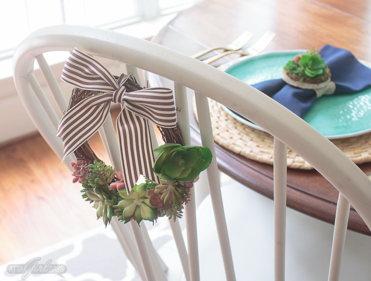 A white chair with a succulent grapevine wreath tied to the back of it. In the background, there's an aqua blue plate on top of a woven natural charger. A navy blue napkin, tied with a DIY succulent napkin ring miniature dish garden, rests on top of the plate.