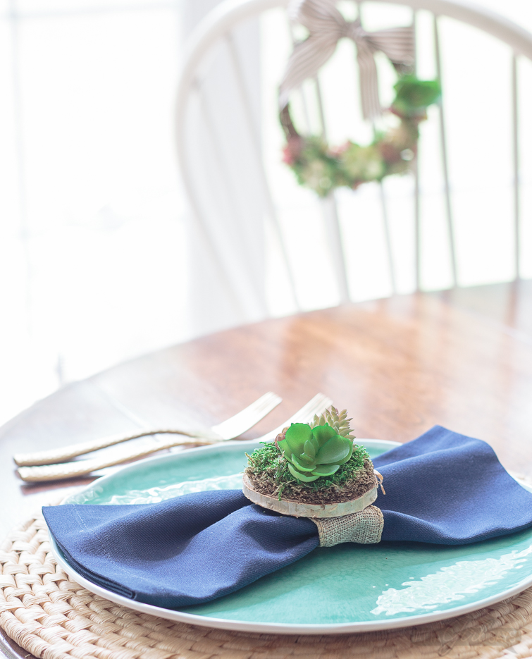 A dinner table place setting featuring an aqua blue plate on a woven seagrass charger. There's a navy blue napkin on the plate with a miniature succulent garden napkin ring. A grapevine succulent wreath hangs on a chair in the background.