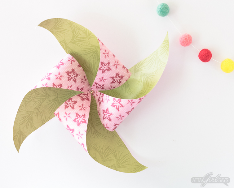 Learn how to make a pinwheel using a full sheet of scrapbook paper. Hang larger pinwheels on the wall or on your front door to create an instant party vibe! #papercrafts #pinwheels #scrapbookpaper #papercrafting